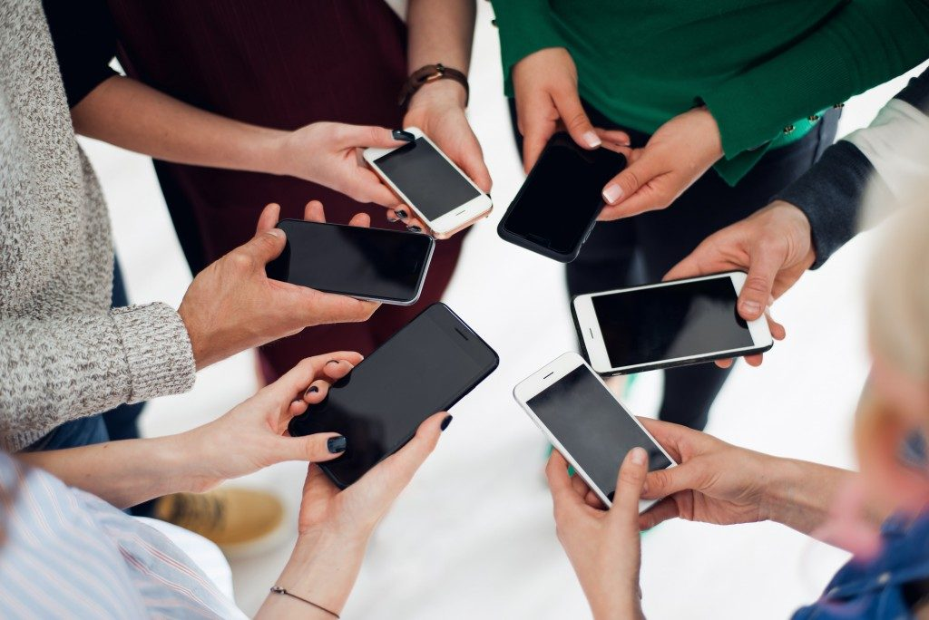 group of colleagues using their smartphones in a huddle