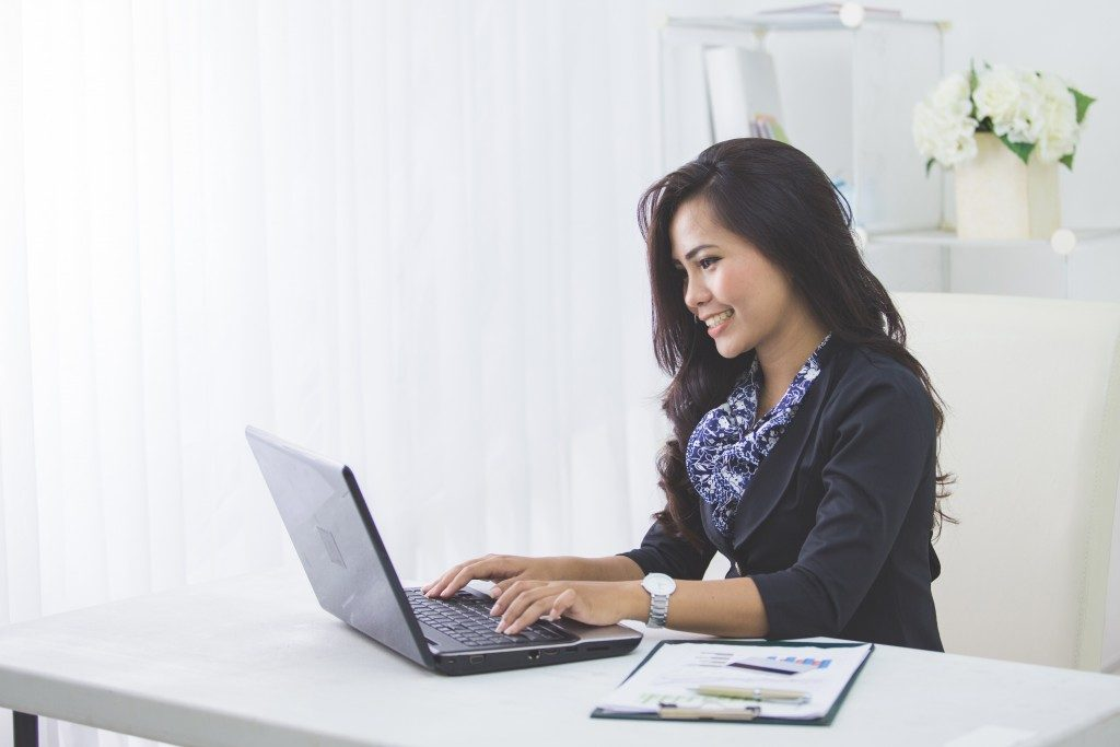 woman working with laptop on her desk