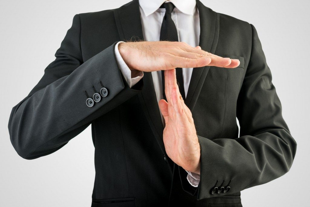 business man doing time out handsign