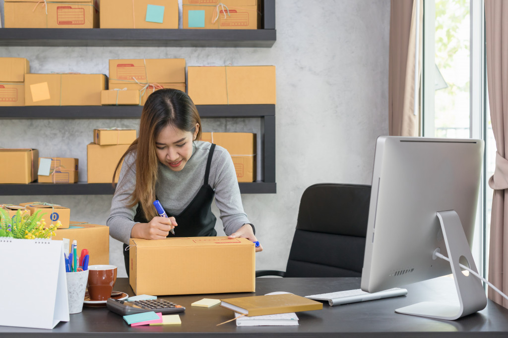 a person writing on a box in front of her computer